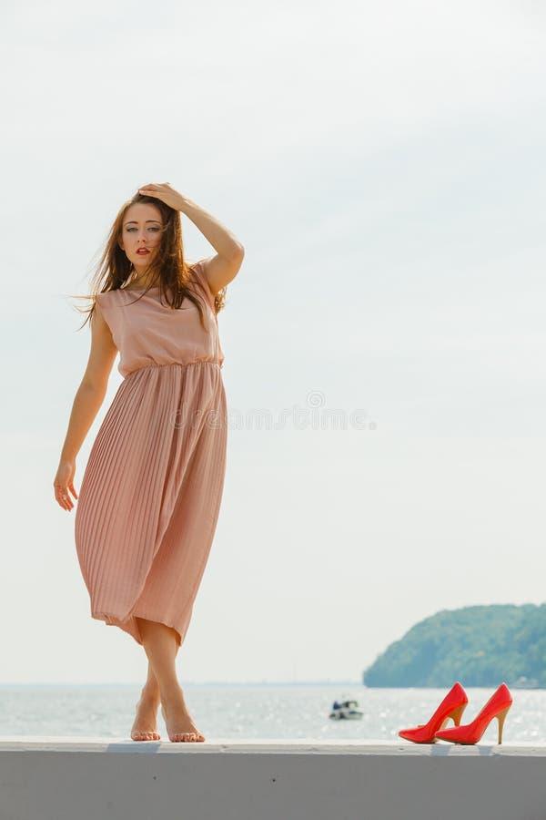 Femme portant la longue robe rose-clair sur la jetée images libres de droits