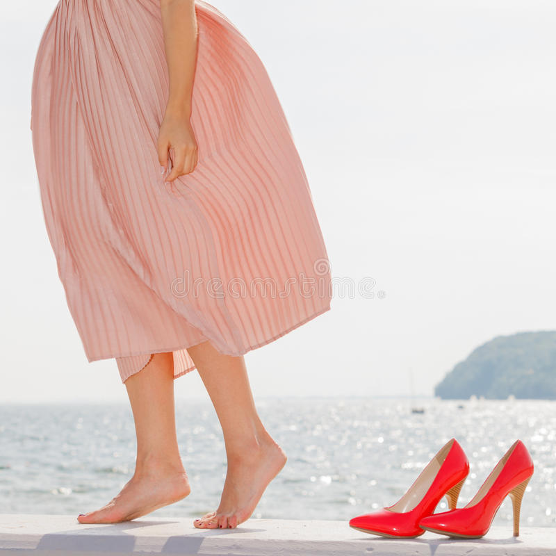 Femme portant la longue robe rose-clair sur la jetée photographie stock libre de droits
