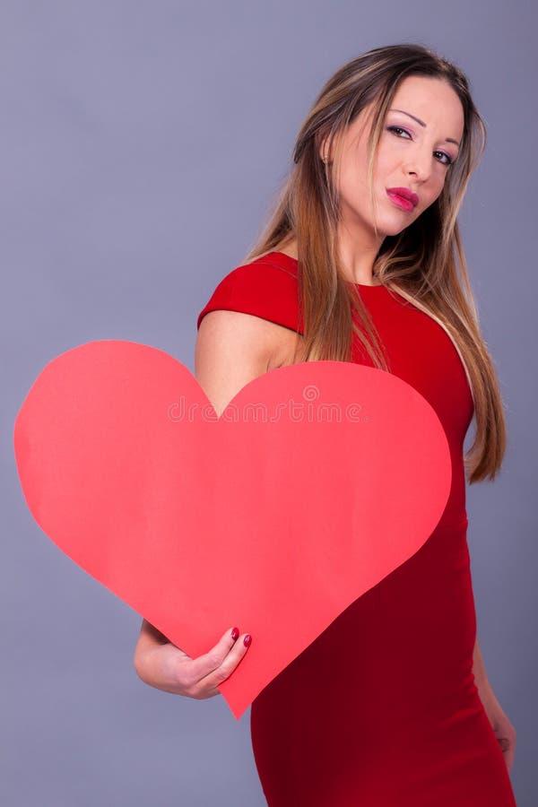 Femme portant la robe rouge tenant le grand symbole d'amour de signe de coeur photo stock