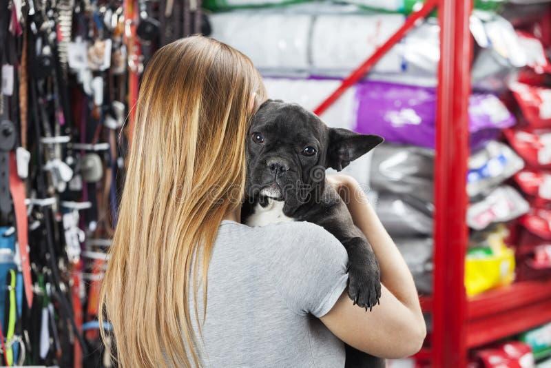 Femme portant le bouledogue français au magasin d'animal familier photo stock