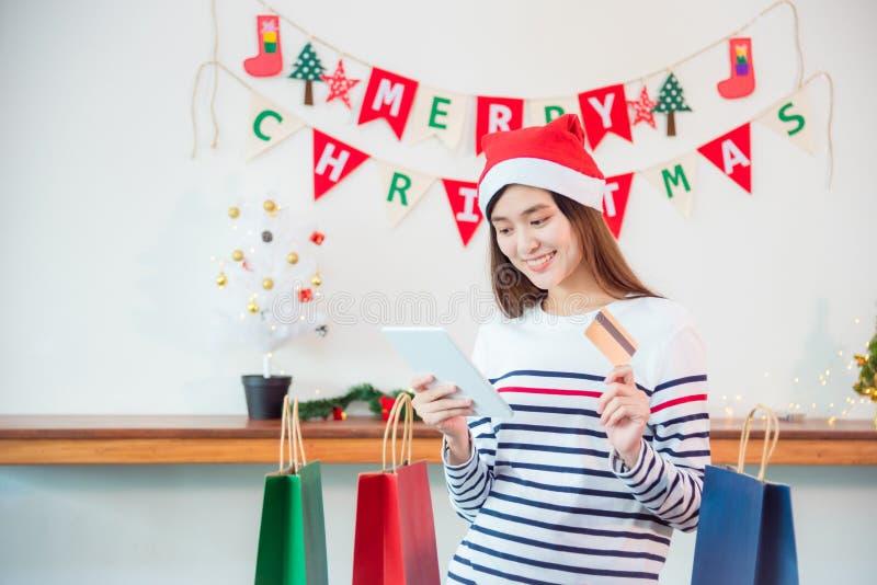 Femme portant le cadeau de achat de Noël de chapeau de Santa en ligne image libre de droits