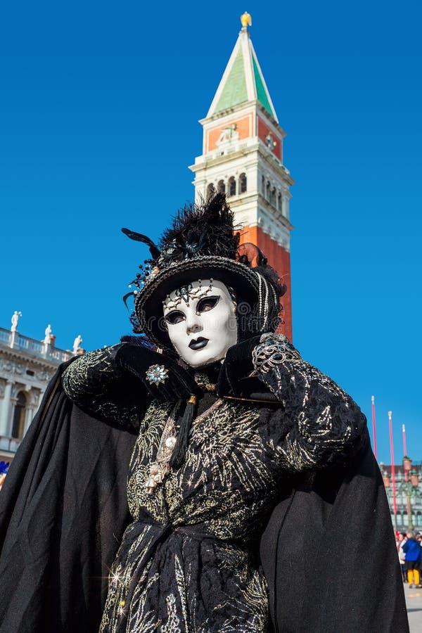 Femme portant le costume noir et le masque blanc sur le carnaval vénitien photo libre de droits