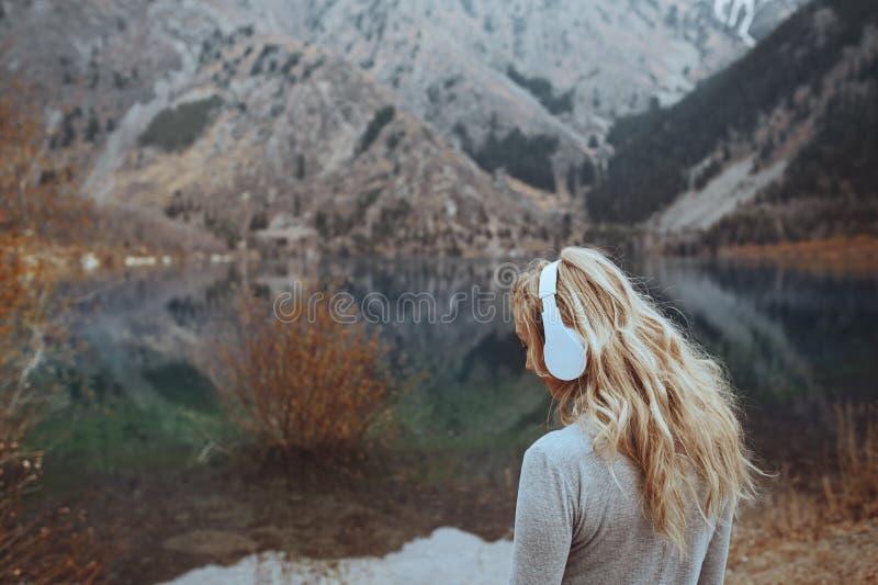 Femme portant le headshot sans fil au lac de montagne image libre de droits