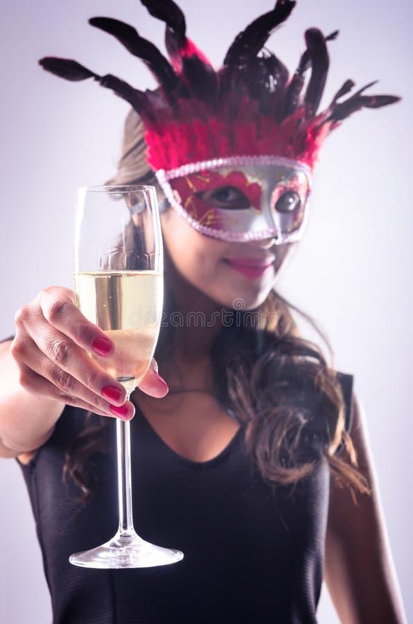Femme portant le masque rouge au champagne potable de partie de mascarade images stock