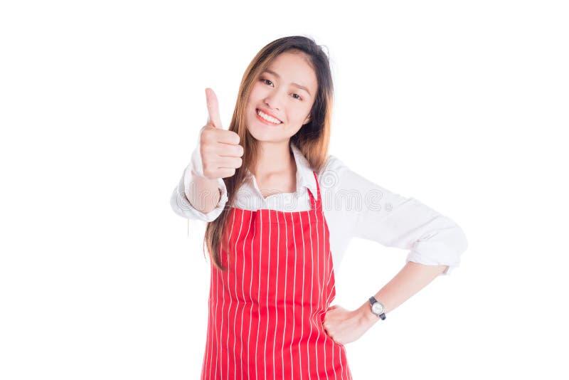 Femme portant le tablier rouge, souriant et montrant le pouce  images stock