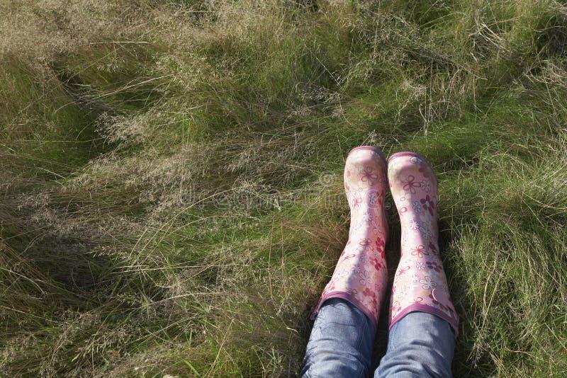 Femme portant les couvre-chaussures roses se trouvant sur l'herbe image stock