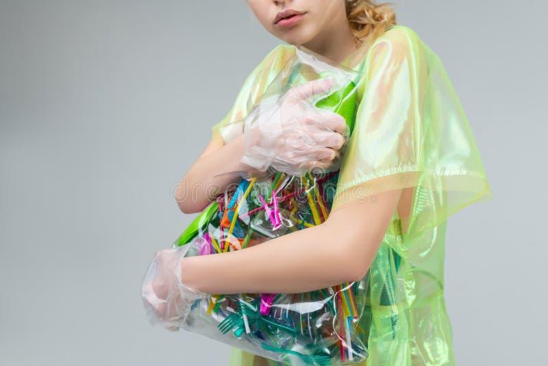 Femme portant les gants transparents tenant le sac avec les articles en plastique photo stock