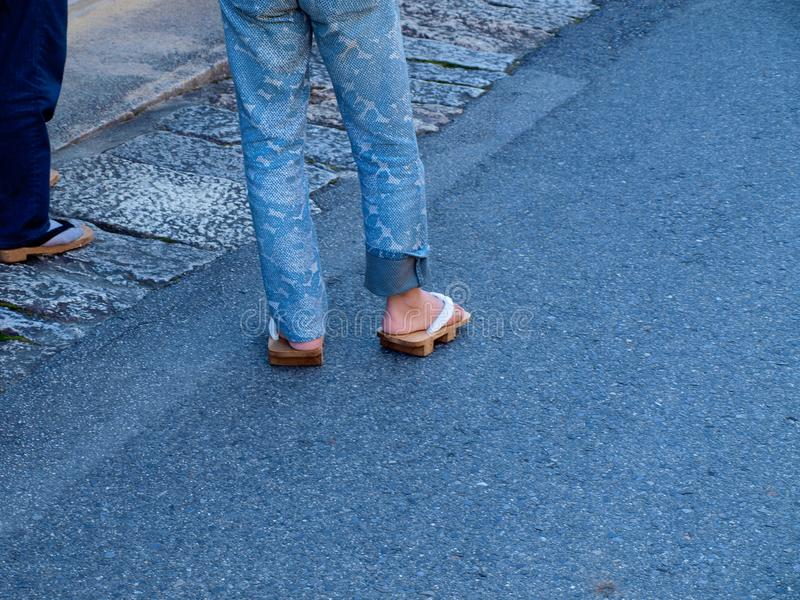 Femme portant les sandales japonaises traditionnelles avec des jeans sur le St images libres de droits
