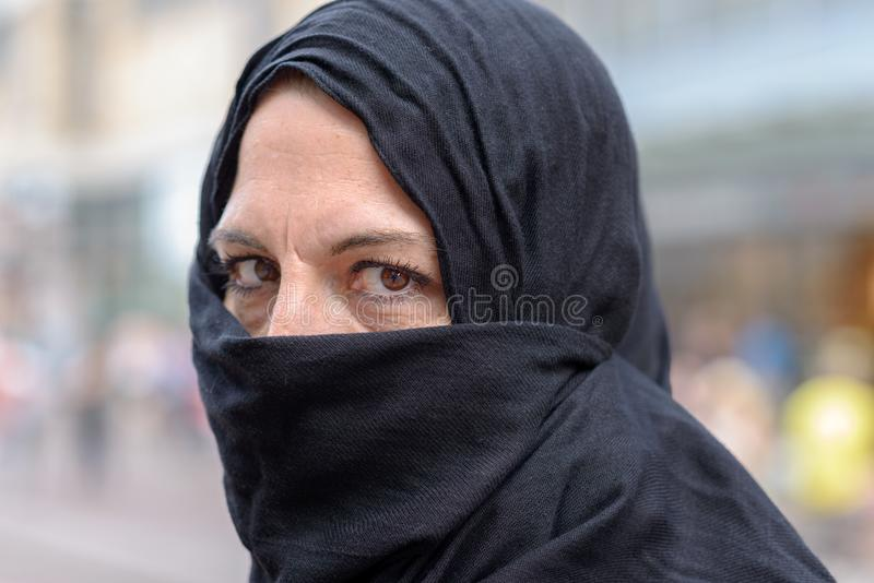 Femme portant un hijab avec la bouche couverte images stock