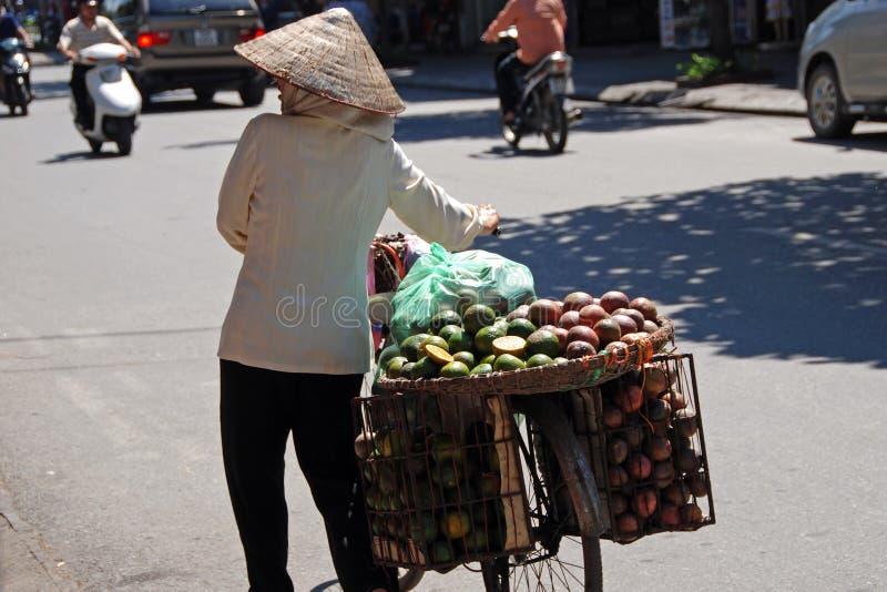 Femme portant un panier de fruit à Hanoï images libres de droits