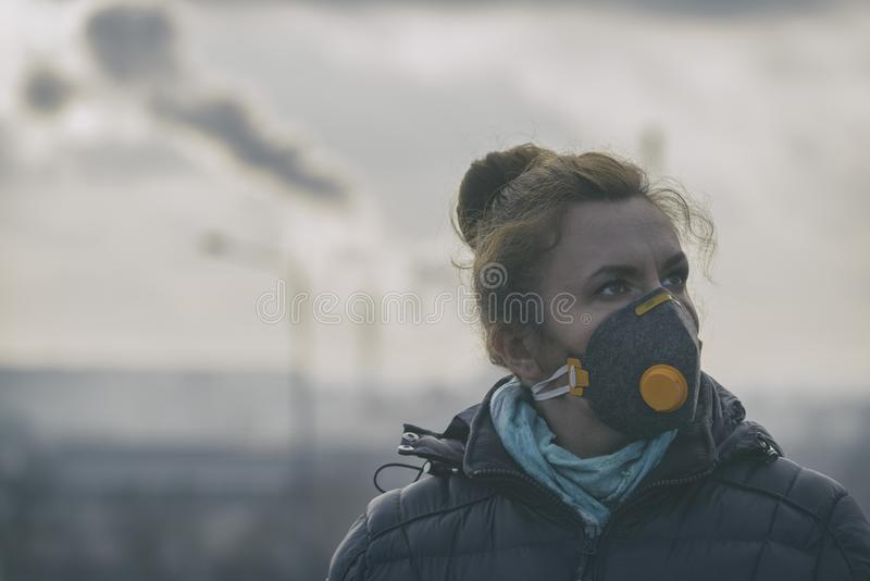 Femme portant un vrai masque protecteur contre la pollution, d'anti-brouillard enfumé et de virus photographie stock libre de droits