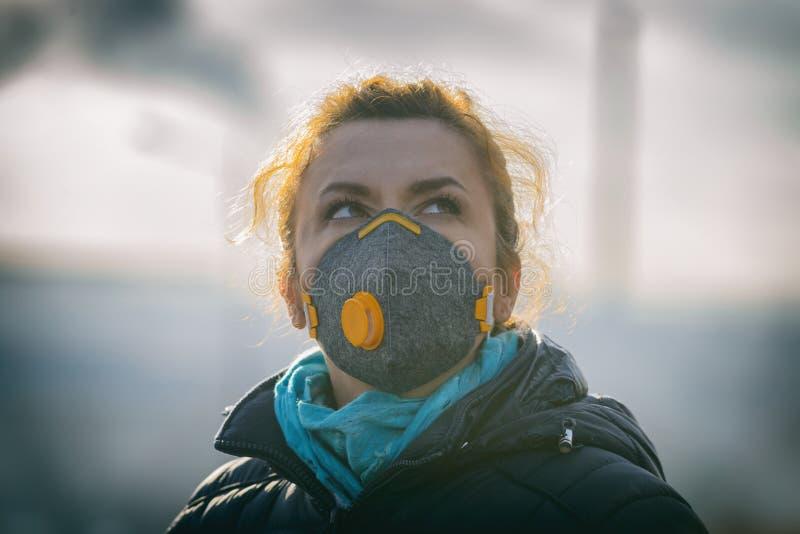 Femme portant un vrai masque protecteur contre la pollution, d'anti-brouillard enfumé et de virus photographie stock