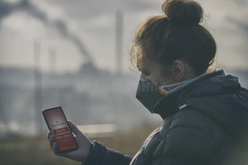 Femme portant un vrai masque protecteur d'anti-brouillard enfumé et vérifiant la pollution atmosphérique actuelle avec l'appli fu images libres de droits