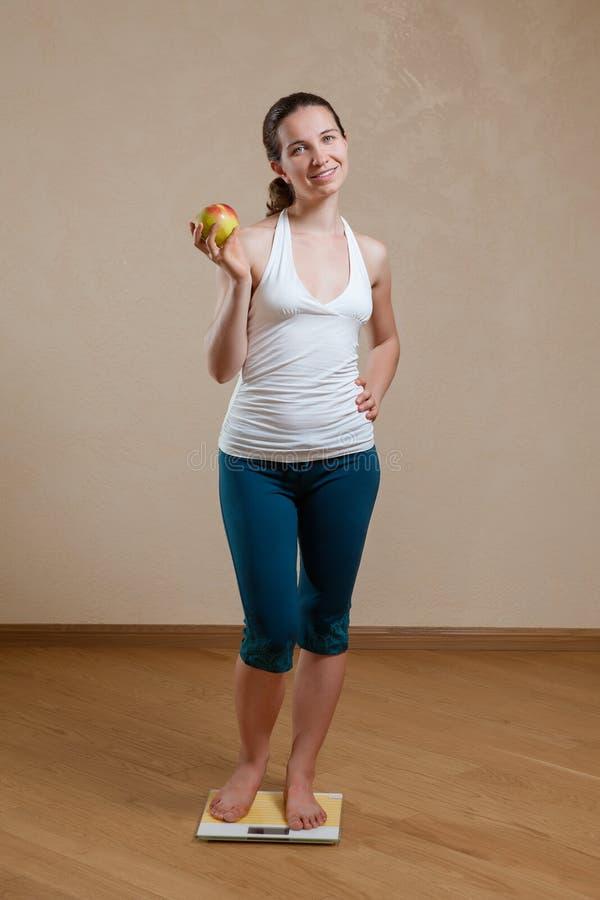 Femme posant aux échelles avec la pomme photographie stock