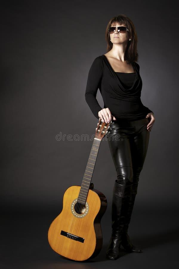 Femme posant avec la guitare sur l'étage. photos libres de droits