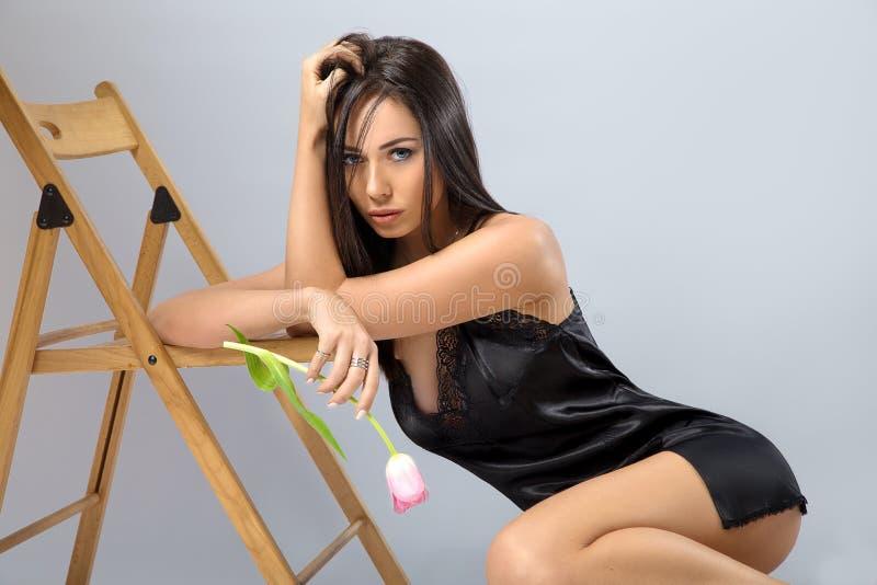 Femme posant dans la lingerie noire avec la fleur photographie stock libre de droits