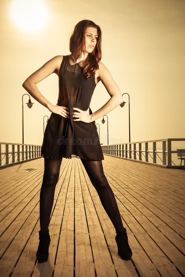Femme posant sur le pilier au lever de soleil images stock