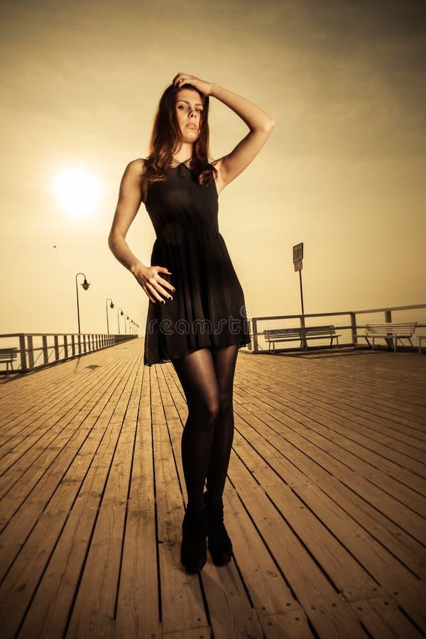 Femme posant sur le pilier au lever de soleil images libres de droits