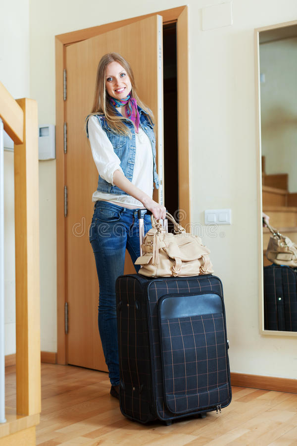 Femme positive avec la valise près de la porte photographie stock