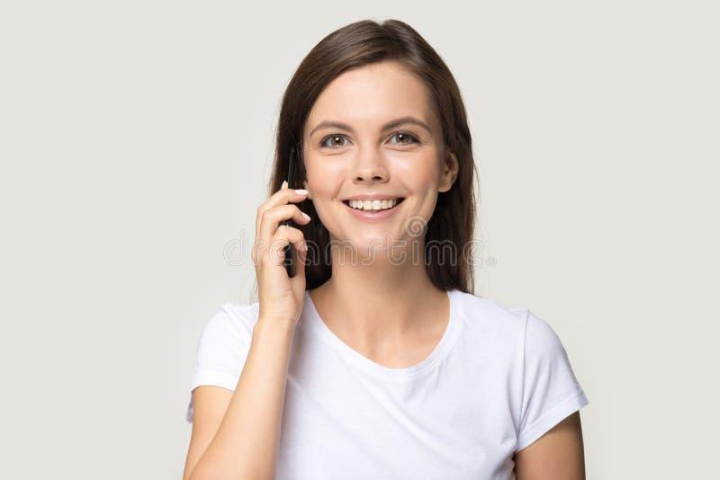 Femme positive de portrait de Headshot parlant au téléphone d'isolement sur gris images libres de droits