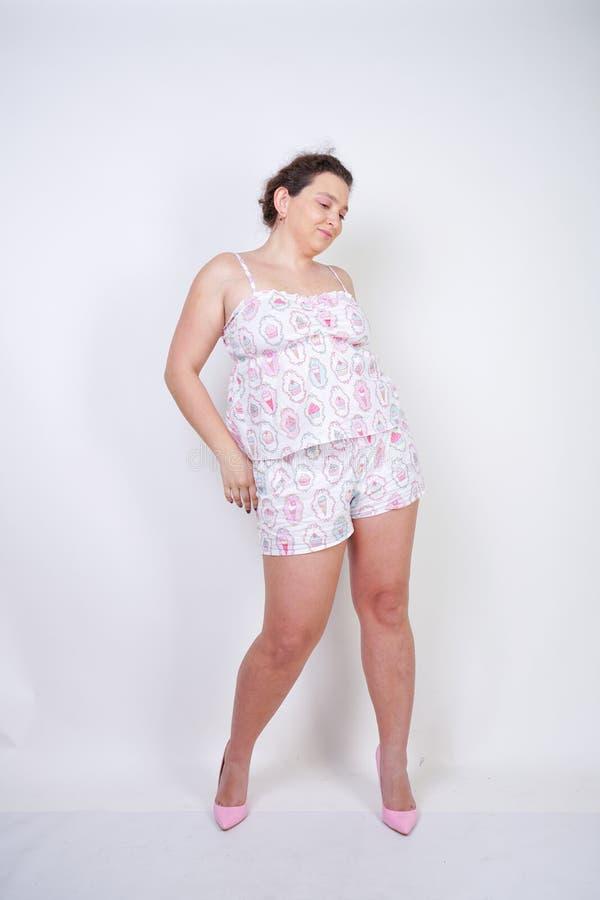 Femme potel?e sinueuse dans les supports dr?les de pyjamas et stretchintg sur un fond blanc dans le studio photographie stock
