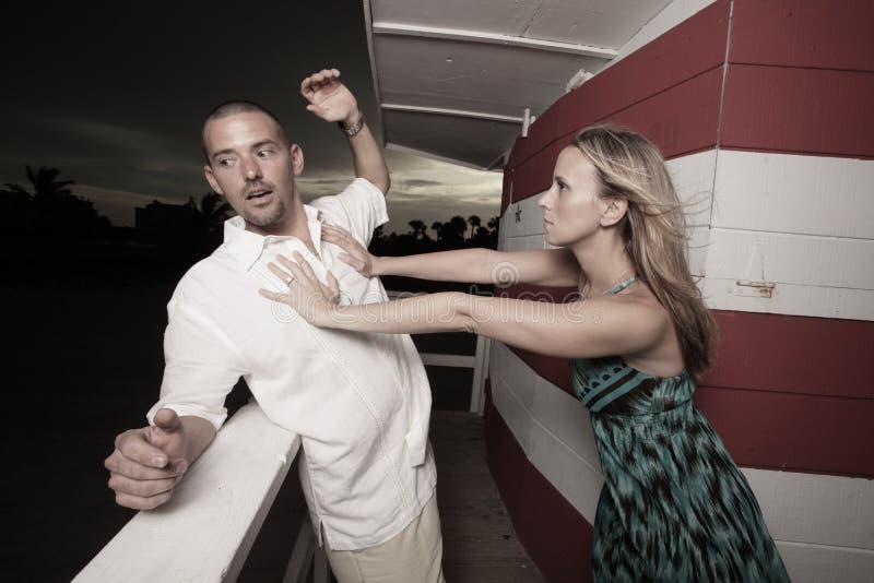Femme poussant l'homme au-dessus du bord photographie stock