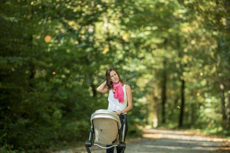Femme poussant la voiture d'enfant en parc image stock