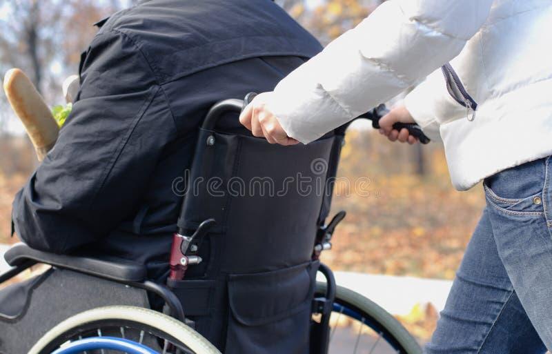 Femme poussant un homme handicapé dans un fauteuil roulant images libres de droits