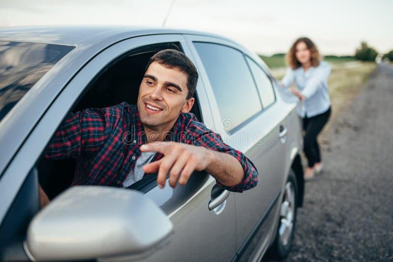 Femme poussant une voiture cassée, conducteur d'homme photographie stock libre de droits