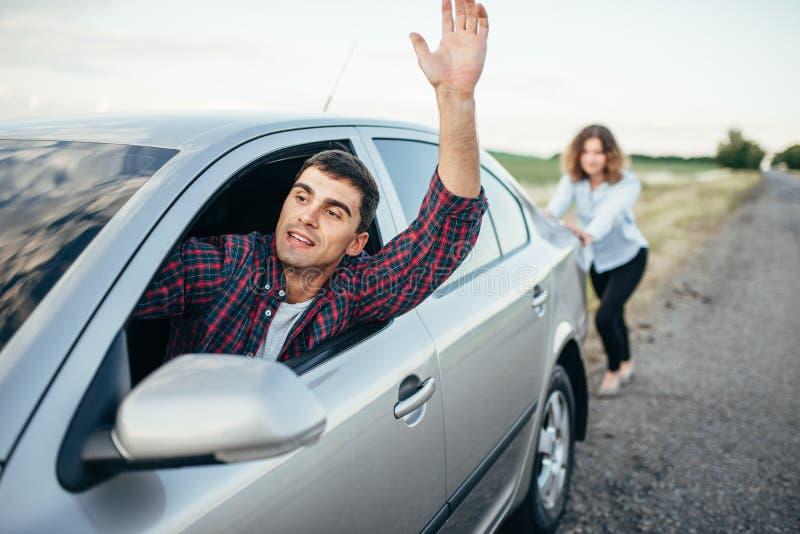 Femme poussant une voiture cassée, conducteur d'homme images stock