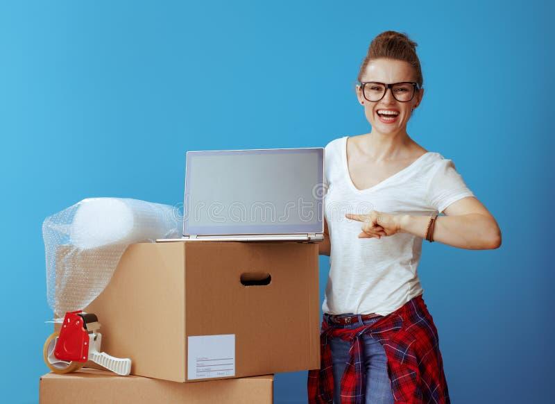 Femme près de boîte en carton dirigeant l'écran vide d'ordinateur portable sur le bleu images libres de droits