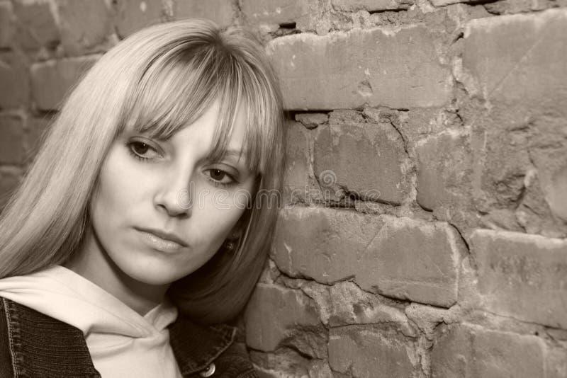 Femme près du mur de briques image libre de droits