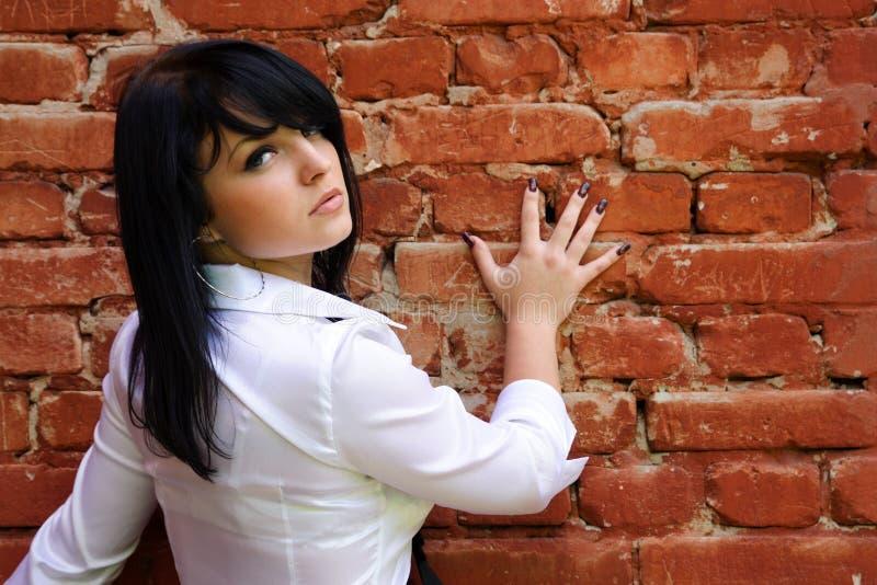 Femme près du mur de briques images stock