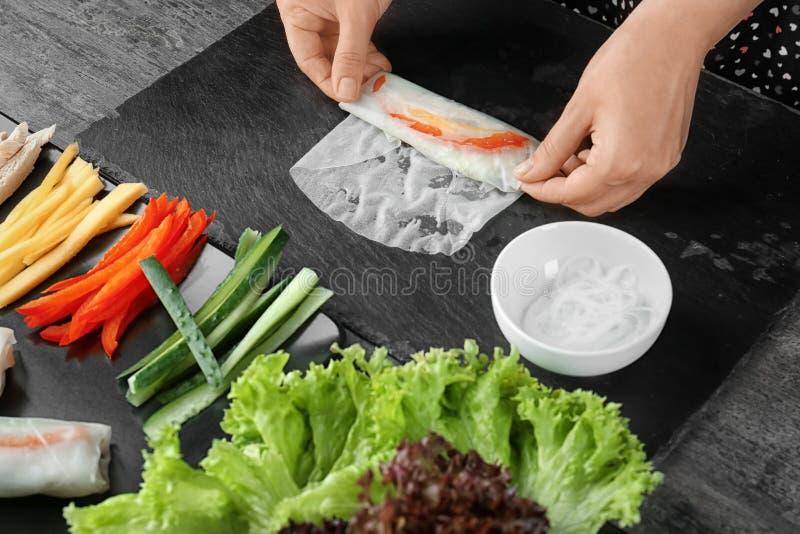 Femme préparant des petits pains de ressort en papier de riz image libre de droits