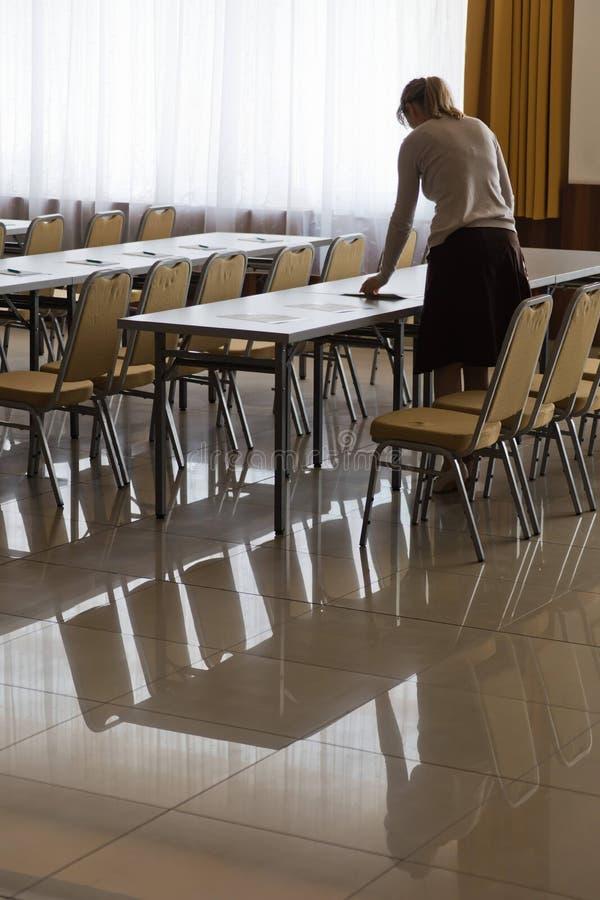 Femme préparant des tables dans la salle de conférence images stock