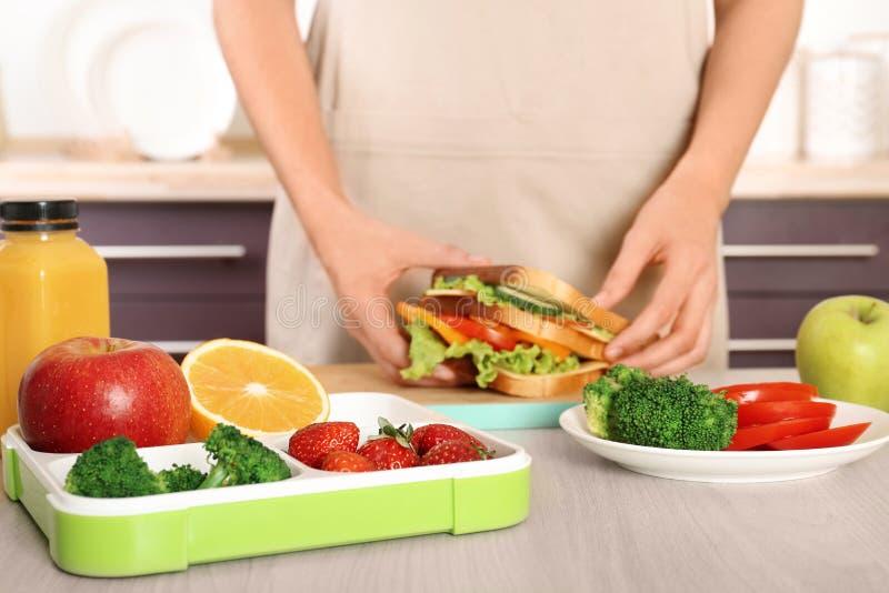 Femme préparant la nourriture pour son enfant à la table dans la cuisine, plan rapproché image stock