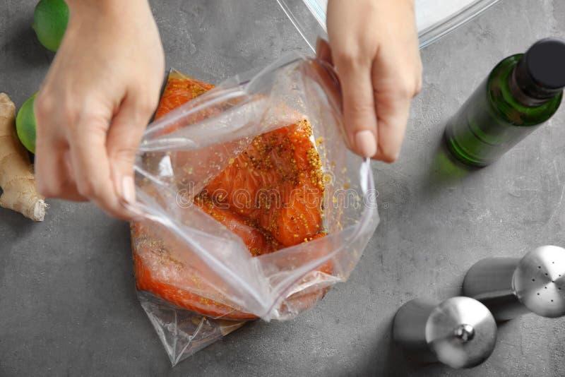 Femme préparant le filet saumoné avec la marinade de moutarde de miel dans le sac de serrure de fermeture éclair image libre de droits
