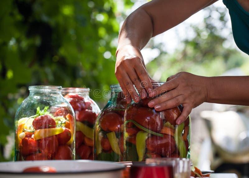 Femme préparant les conserves de légumes dans le pot en verre à la nature photographie stock