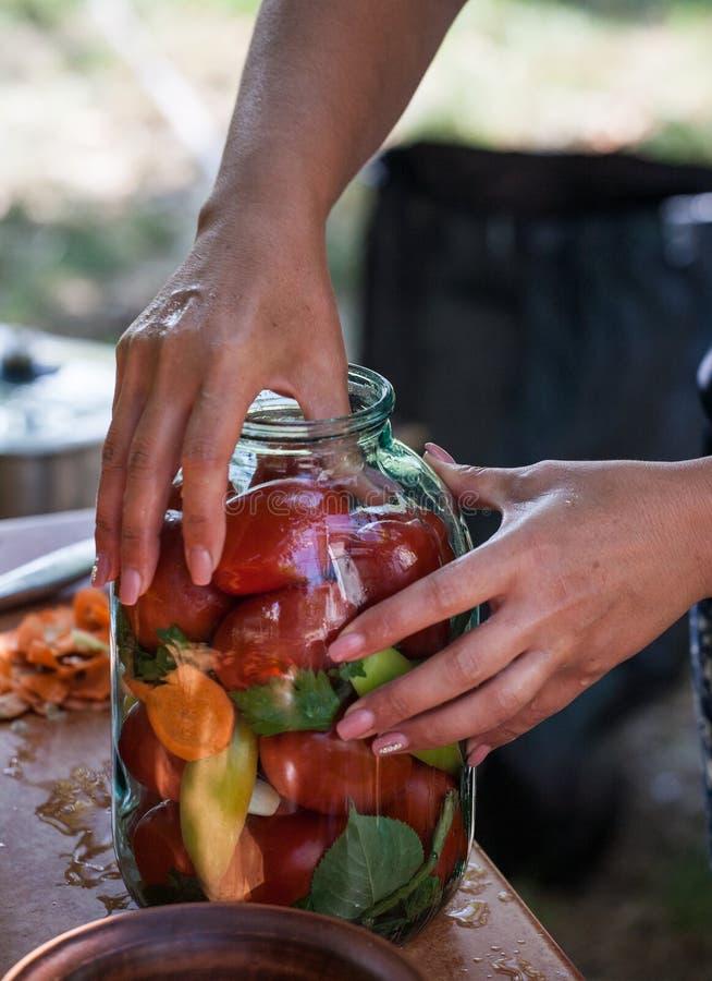 Femme préparant les conserves de légumes dans le pot en verre image libre de droits