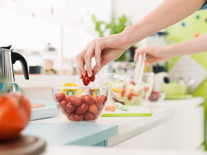 Femme préparant une salade saine fraîche photos stock