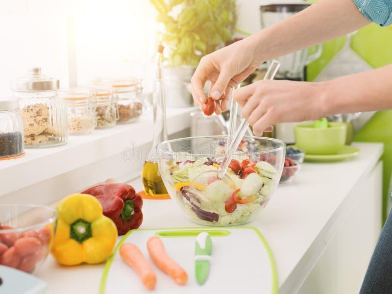Femme préparant une salade saine fraîche image libre de droits
