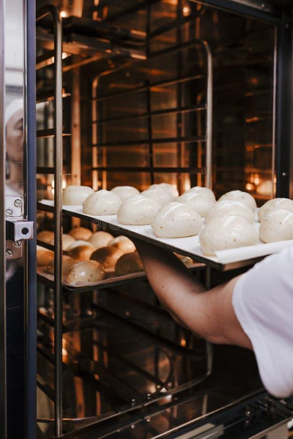 Femme présentant la cuisson de pain en four Four de production ? la boulangerie Pain de cuisson Fabrication de pain photographie stock