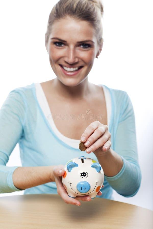 Femme présentant une pièce de monnaie dans une tirelire photographie stock