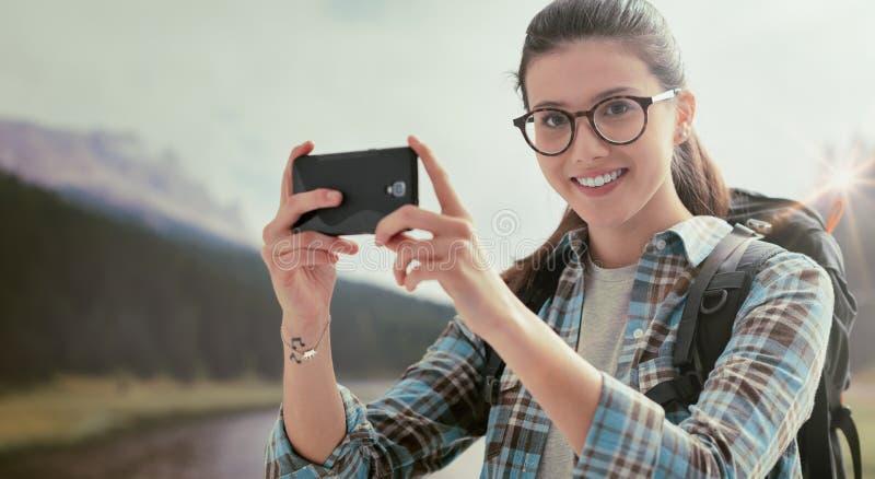 Femme prenant à photos de nature avec elle le téléphone image stock