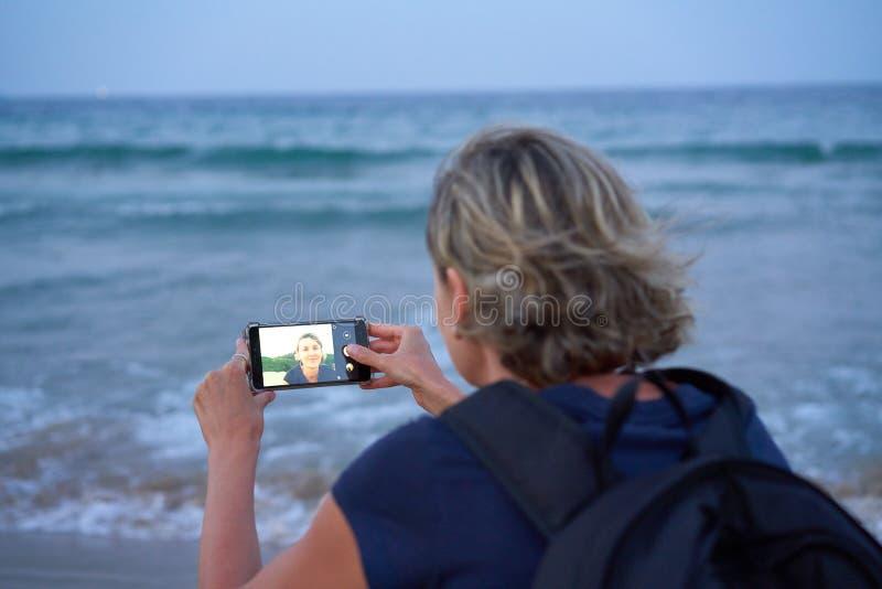 Femme prenant ? un autoportrait au t?l?phone intelligent la plage sur le coucher du soleil ? photographie stock libre de droits