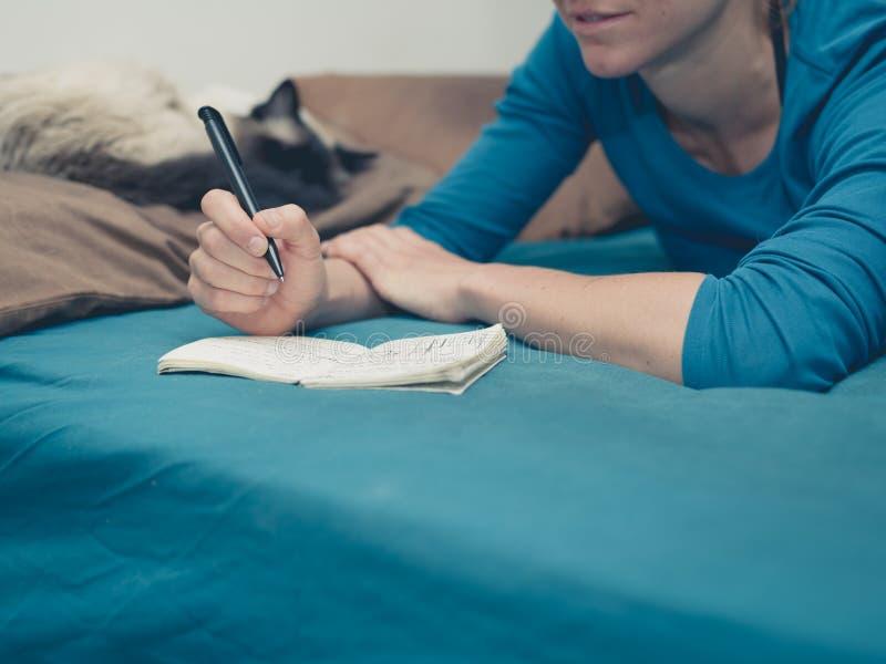Femme prenant des notes dans le lit avec le chat photographie stock