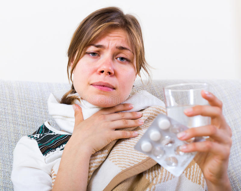 Femme prenant l'antibiotique contre la douleur de la gorge photo libre de droits