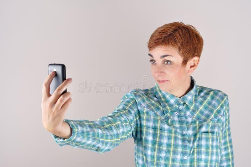 Femme prenant l'autoportrait avec son téléphone intelligent image stock