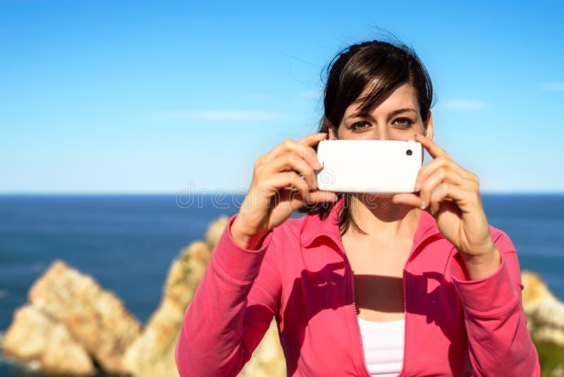Femme prenant la photo avec le téléphone portable l'été photo libre de droits