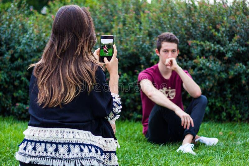Femme prenant la photo de l'homme avec le téléphone intelligent images stock